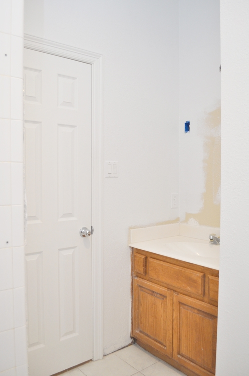 Guest Bathroom Makeover: Old Mirror & Lighting Removed, walls painted white.